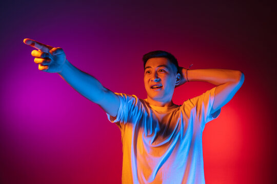 One Asian young man posing isolated on studio background in gradient pink purple neon light, colour filter. Concept of human emotions, facial expression.