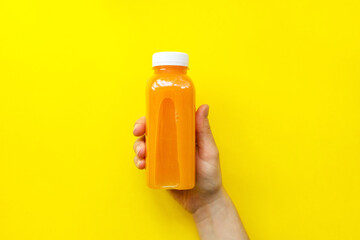 Fototapeta Female hand holding plastic bottles with orange juice or smoothie on yellow background. The concept of diets, detox. Bright background, flat lay, top view obraz