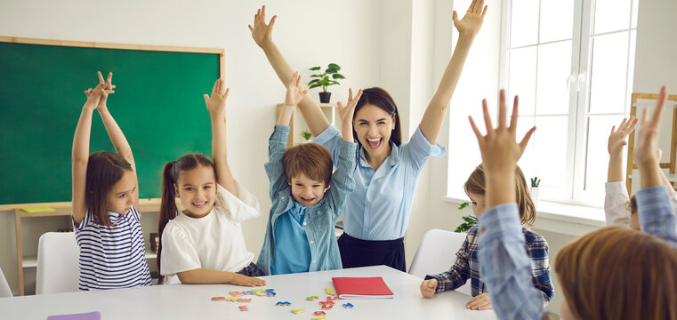 Happy children and educator raising hands up sitting at table in modern classroom. Website header with group portrait of cheerful school teacher and first grade students having fun activities in class
