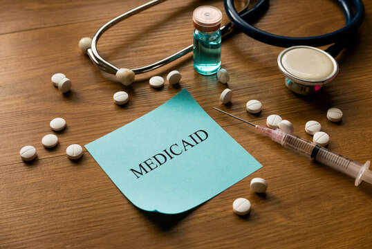 Selective focus of stethoscope, white medical pills, syringe and blue memo note written with Medicaid on wooden background.