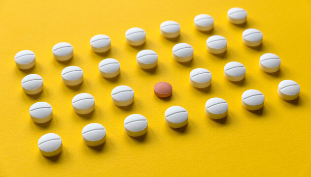 A row of white medical pills and one red pill in the middle  on yellow background.
