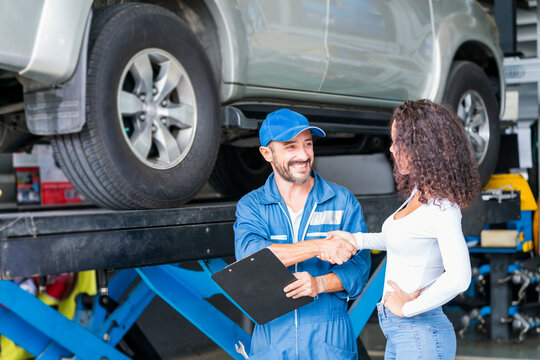 Service repair maintenance concept. The car mechanic is explaining the operation of the engine. Smiling mechanic shaking hands at auto service.