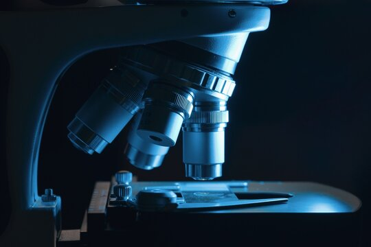 Microscope in laboratory at night. Microbiology and research concept.