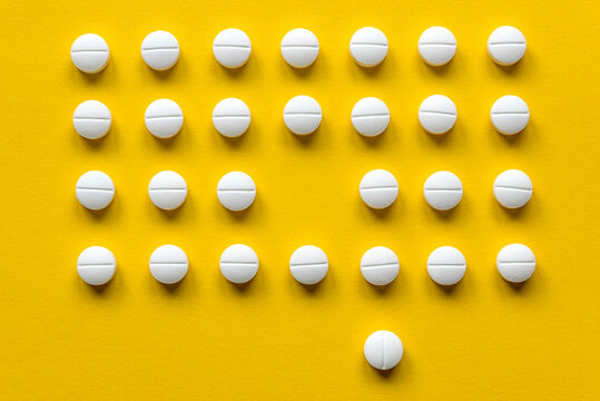 A row of white medical pills on yellow background with one missing spot in the middle and one pill outside the row.