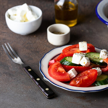 Vegetable salad made from   cucumber, tomato, sweet pepper  and feta cheese, dressing with olive oil in the white blue plate ontable table