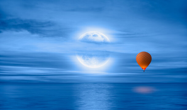 """Hot air balloon flying over calm sea moon at night in the background full """" Elements of this image furnished by NASA"""""""