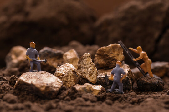 Miniature worker mining stone, metal, gold, lead, copper, zinc and silver. Mining business or Department of Mineral Resources.