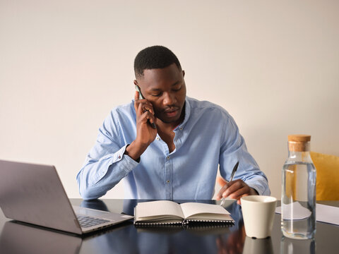 Black male speaking on phone looking at notes in planner