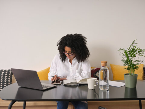Black woman working with smartphone and laptop