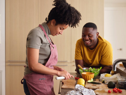 Smiling woman cooking with boyfriend