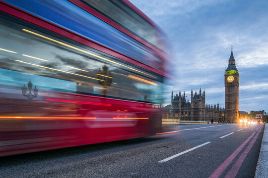 Red double-decker bus crossing the Westminster Bridge in London at night