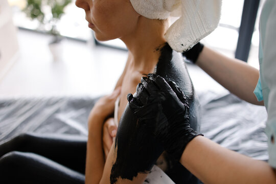 Whole body mud wrap is covered with clay mask. Spa procedure in a luxury salon. Black clay Application treatment. Skin cleansing and treatment. Health and beauty scrub. Relaxation and pleasure resort