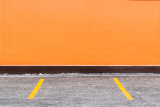 Orange Building Wall And Parking Spaces With Painted Yellow Dividers