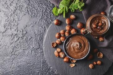 Fototapeta Bowl and jar with tasty chocolate paste and hazelnuts on dark background obraz