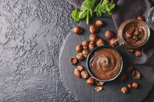 Bowl and jar with tasty chocolate paste and hazelnuts on dark background