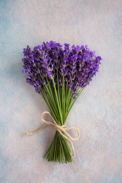Bouquet of lavender flowers tied with rope on colored decorative plaster background