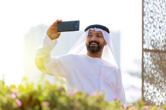 Middle Eastern Arab Emirati Vlogger holding mobile phone