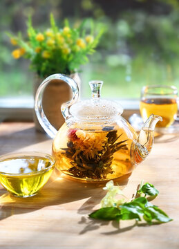 Glass tea pot with a blooming tea flower