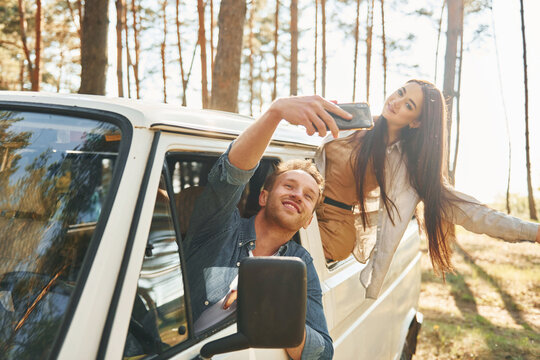 Making selfie. Young couple is traveling in the forest at daytime together