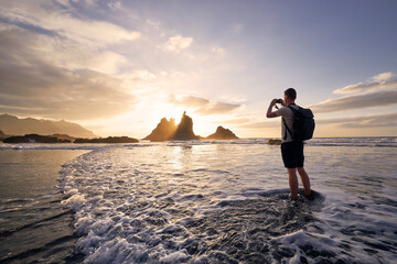 Fototapeta Man during photographing landscape with cliff. Young photographer on beach at beautiful sunset. Tenerife, Canary Islands, Spain. obraz