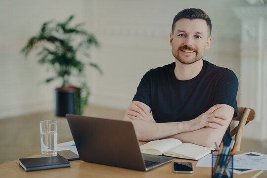 Handsome successful freelancer working with laptop at his workplace