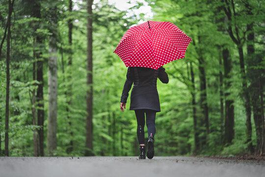 Frau mit rotem Regenschirm auf Waldweg