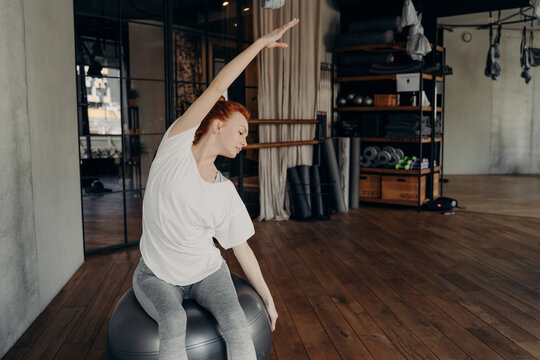 Young sportive female sitting on large silver exercise ball and stretching