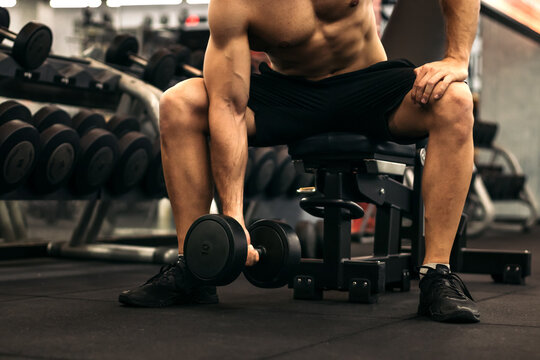 Muscular man training arm with a dumbbell