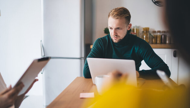 Young serious male using laptop in coworking space