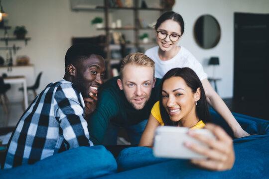 Glad multiethnic partners taking selfie on smartphone on sofa