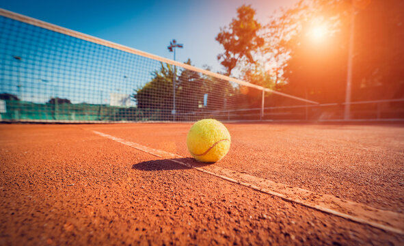 Wide angle close-up photograph of tennis ball on court during sunset. Competitive individual sports concept.