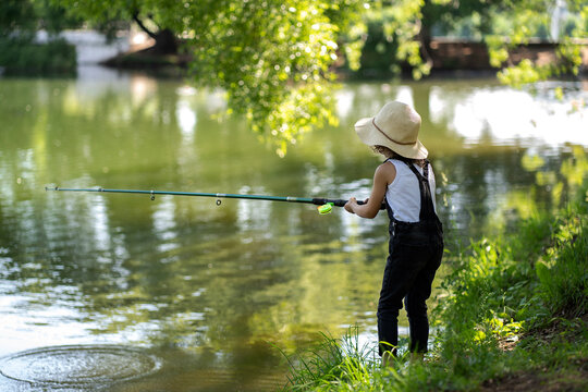 A little girl with curly hair in a straw hat and black overalls stands with a fishing rod by the pond. Child fishing on a summer day