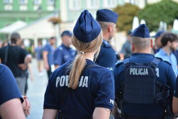 Obraz Kobiety policjantki w polskiej policji na zabezpieczeniu imprezy.  - fototapety do salonu
