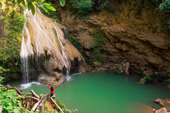 A woman red shirted is admiring the beauty of a green waterfall in the middle of a forest and mountain, and beautiful nature, Koh Luang Waterfall, Lamphun