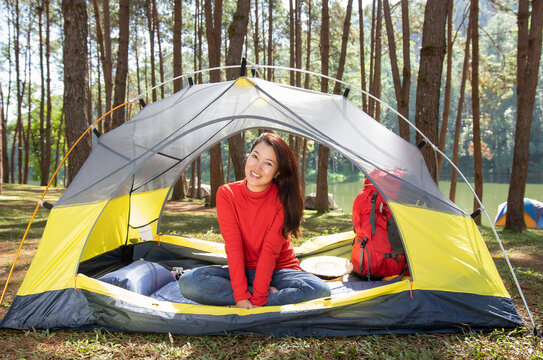 A beautiful woman in a red shirt camping, sitting in a yellow tent with red backpack In the middle of a pine beautiful forest beside a lake, Pang Oung, Mae Hong Son, Thailand.