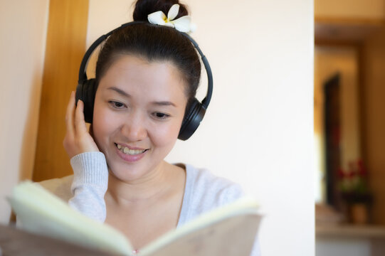 Asian teenage girl reading and listening to music happily.