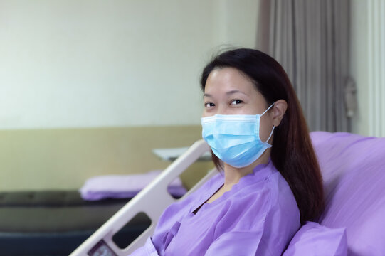 Young Asian female patient is smiling and showing medical mask. Patient feels happy and comfortable with treatment and therapy on hospital bed in hospital room. Medical healthcare concept.