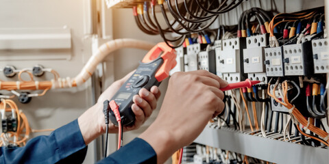Electrician engineer uses a multimeter to test the electrical installation and power line current...