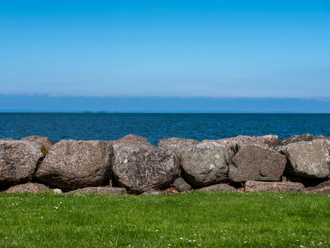 Green grass stone wall and blue water and sky in layered image. Abstract with copy space