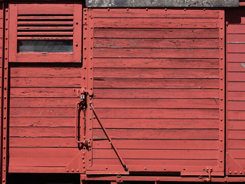 Side and door of old wooden train wagon with weathered red boards.