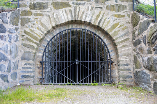 Medieval stone arch leading into a tunnel. Locked black iron gate. Part of defences of old Gothenburg, Sweden.