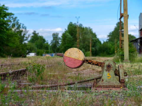 Rusty gear by railroad track. Grass and weeds showing. Shot in Sweden, Scandinavia
