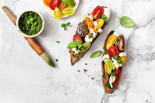 Bruschetta sandwiches with tomatoes,burrata cheese and pesto. Traditional  - grilled bruschetta toasts.