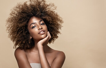 Fototapeta Beauty portrait of african american woman with clean healthy skin on beige background. Smiling dreamy beautiful afro girl.Curly black hair obraz