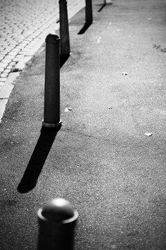 Pfosten am Straßenrand, die harte Schatten im Sonnenlicht werfen