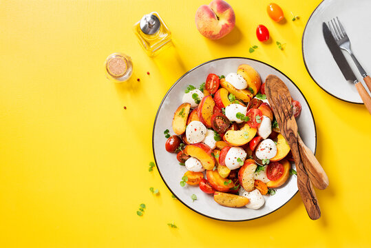 Summer peach Caprese salad with mozzarella and cherry tomatoes. Yellow background. Top view.