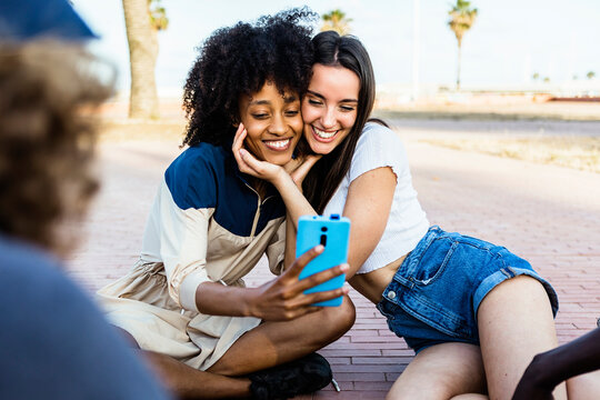 Happy multiracial women taking a selfie with smart phone outdoors - Joyful multiethnic female couple having fun with their friends in summer holidays - Millennial generation, friendship and youth
