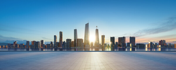 Panoramic view of empty concrete tiles floor with city skyline.