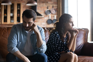 Obraz Angry young husband and wife sitting together, hating, ignoring each other, feeling stress, fatigue. Sad couple having relationship crisis, needing family counseling support. Family problems concept - fototapety do salonu