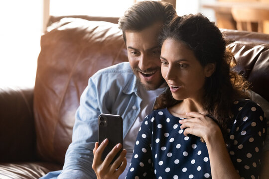 Shocked happy couple with smartphone reading message, getting surprising unbelievable good news from video call, using mobile phone together, staring at screen in amazement, sitting on couch at home